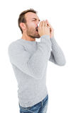 Young man holding a tissue and sneezing Royalty Free Stock Photo
