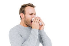 Young man holding a tissue and sneezing Royalty Free Stock Photos