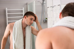 Young man holding towel on his shoulders while viewing a mirror Stock Photo
