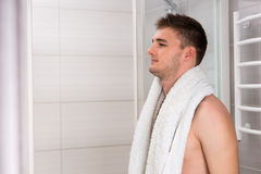 Young man holding towel on his shoulders after washing procedure Stock Image