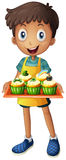 A young man holding a tray with cupcakes Stock Image