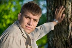 The young man holding from a tree Stock Photo