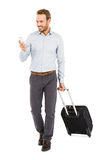 Young man holding trolley bag and using mobile phone Royalty Free Stock Image