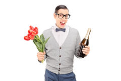 Young man holding tulips and a champagne Royalty Free Stock Photos