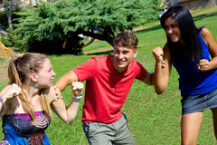 Young man holding two girls fighting for him Stock Photo