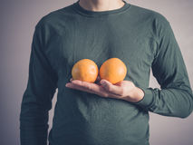 Young man holding two oranges. A young man wearing a green top is holding two oranges Royalty Free Stock Images