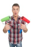 Young man holding two painting rollers. Royalty Free Stock Photo