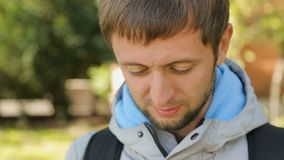 Young man holding and typing mobile phone in hands, using application, search. Stock footage stock footage