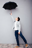 Young man holding umbrella Stock Images