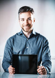 Young man holding up a blank tablet-pc royalty free stock image