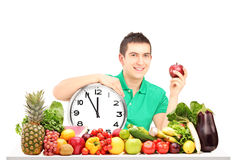 Young man holding a wall clock and apple, sitting on a table ful Royalty Free Stock Photos