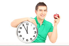 Young man holding wall clock and red apple on a table Stock Photo