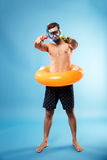 Young man holding water guns and swimmng circle. Young bearded serious man in swimming glasses holding water guns and swimmng circle isolated over blue Royalty Free Stock Photos