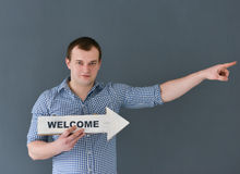 Young man holding welcome board banner and pointing something, standing on dark background Stock Photography