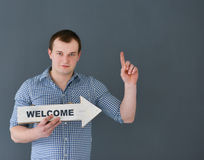 Young man holding welcome board banner Royalty Free Stock Image