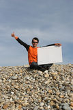 Young Man Holding White Card. At the beach royalty free stock image