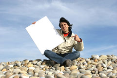 Young Man Holding White Card. At the beach royalty free stock images