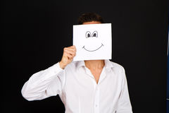 Young man holding white card with a happy face Stock Photo