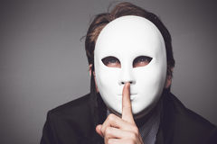 Man in white mask. Young man in white mask over asking for silence on a gray background Royalty Free Stock Images