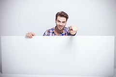 Young man holding a white panel Royalty Free Stock Photo