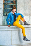 Young Man holding white rose, waiting for you on street. Man Waiting for You. Dressing in a blue jacket with hood, black underwear, yellow pants, leather boot Royalty Free Stock Photography