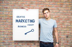 Young man holding whiteboard with marketing content. Royalty Free Stock Photos