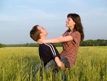 Young man Holding Wife in Field Smiling. Looking each other Stock Photography