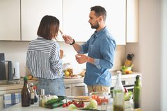 Young man holding wine cork while his girlfriend smelling it royalty free stock images