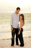 Young man holding woman in front of ocean looking. A tall handsome yooung man is holding a beautiful sexy woman close and looking down at her smiling as she Royalty Free Stock Photos