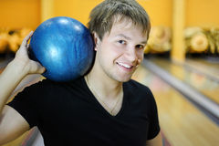 Young man holds ball in bowling club. Young smiling man wearing in black t-shirt holds blue ball in bowling club Royalty Free Stock Photos