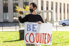 A young man holds a banner that says be Counted referring to vote counting