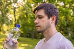 Young man holds bottle with water in hand stock images