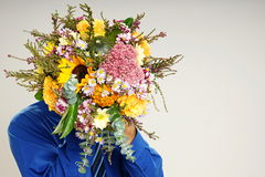 Young man holds bouquet of flowers Royalty Free Stock Photography