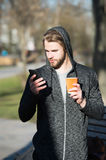 Young man holds coffee, tea paper cup, phone in jersey Royalty Free Stock Images