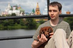 Young man holds dachshund on hands outdoor Stock Photos