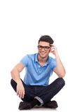 Young man holds head while sitting Stock Photography