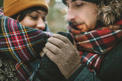 Young man holds his girlfriends hands in winter forest Royalty Free Stock Photography