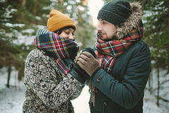 Young man holds his girlfriends hands in winter forest Royalty Free Stock Images