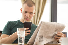 Young man holds the phone reads the newspapers and job search Royalty Free Stock Photos