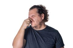 A young man holds or pinches his nose shut because of a stinky smell or odor royalty free stock photo
