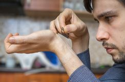 Young man holds razor in hand and wants to commit suicide by cutting vein on hand.  Royalty Free Stock Photography