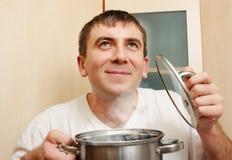 Young man holds a saucepan Stock Photos