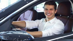 A young man holds the steering wheel of a new car stock photography