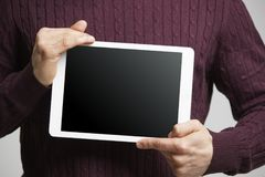 Young man holds a tablet computer showing its screen, mid section stock photo
