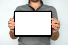 Young man holds a touch pad tablet on isolated white background. Large-size digital tablet with white screen is held by. The man on the blurred backround. A stock image