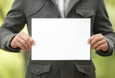 Young man holds up a blank white sign Royalty Free Stock Photography
