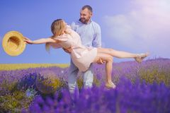 Young man holds woman in lavender field, cute young couple in love walking in a field of lavender flowers. Girl raises her hat up stock image