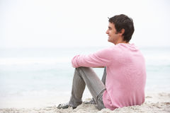 Young Man On Holiday Sitting On Winter Beach. Smiling Royalty Free Stock Photos