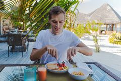 Young man on holiday in a tropical island eating a healthy breakfast royalty free stock photos