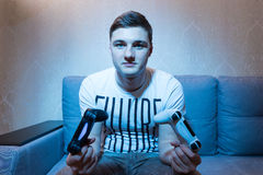 Young man holing two consoles sitting on the sofa at home Royalty Free Stock Photography
